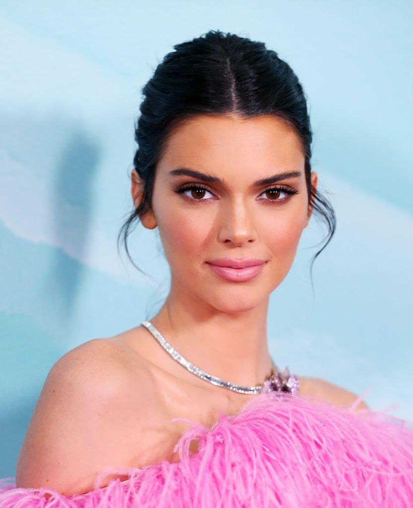 Kendall Jenner em um evento usando colar de diamantes e uma roupa rosa com plumas.