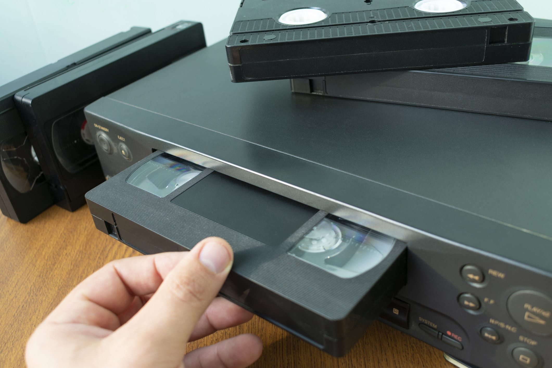 Someone inserts a VHS tape into a VHS player