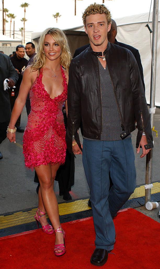 Foto de Britney Spears e Justin Timberlake de mãos dadas em um tapete vermelho.