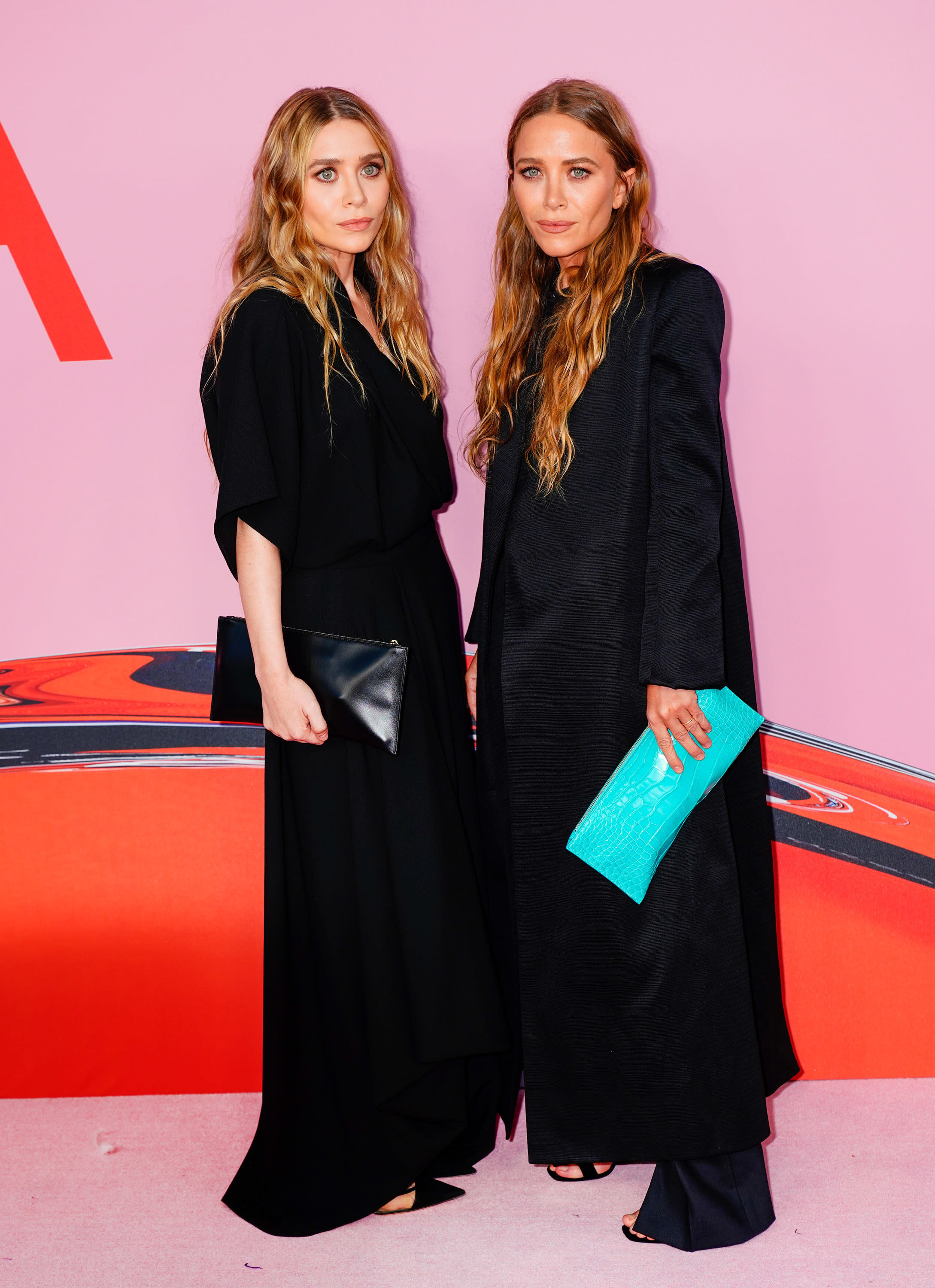 Mary-Kate and Ashley both wear billowy, long, dark colored dresses with sandals. Mary-Kate holds a bright colored snakeskin clutch while Ashley holds a black one.