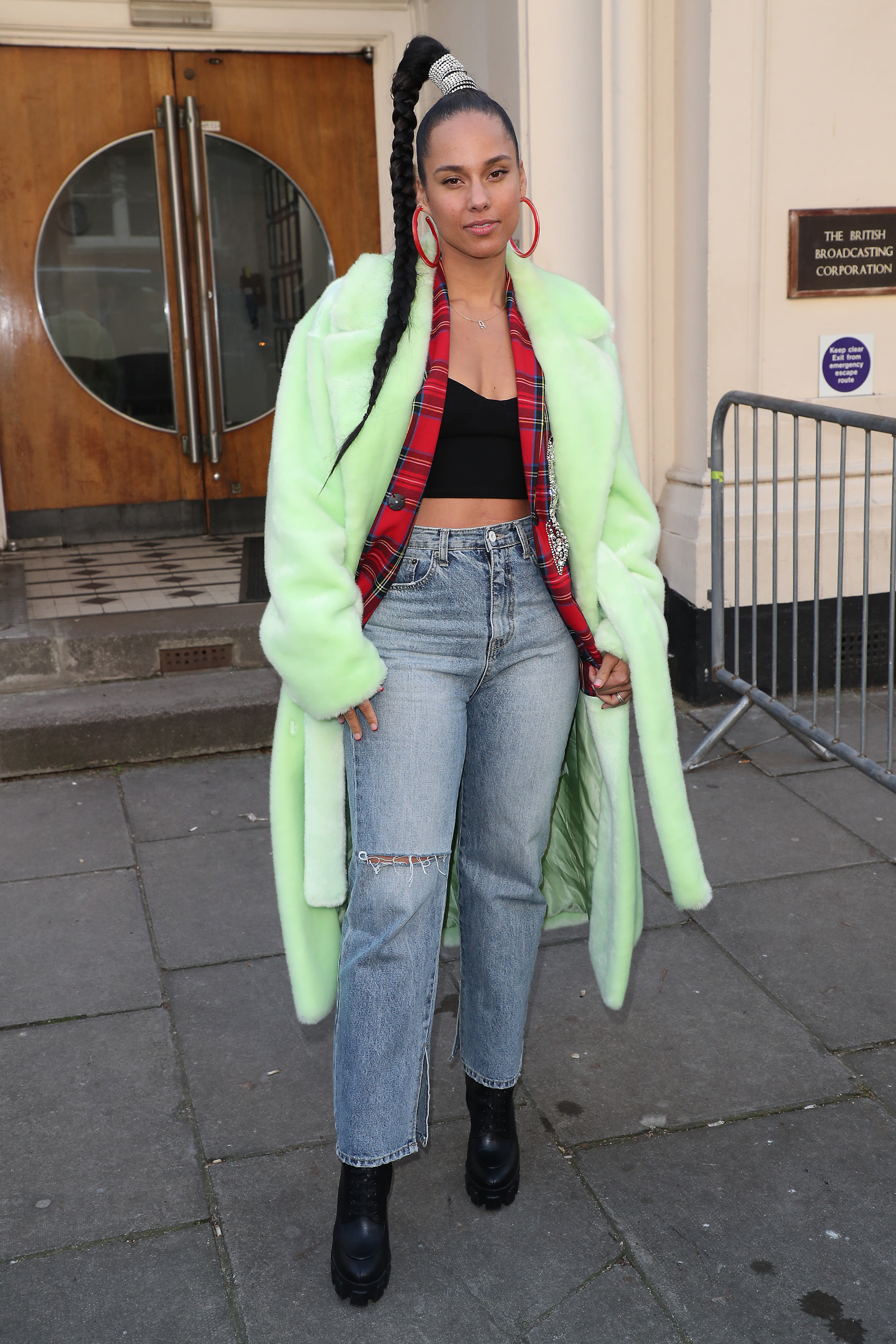Alicia wears a large, furry coat with a plaid patterned blazer underneath and a crop top. She wears straight leg jeans and her hair in a high braid.