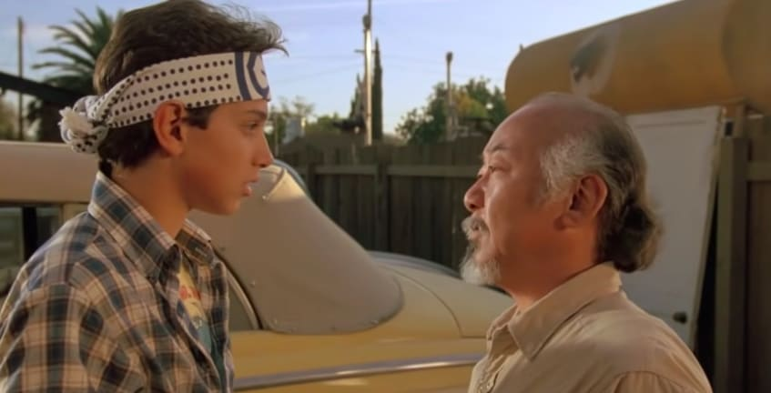 """Ralph Macchio standing in front of the yellow 1947 Ford in """"The Karate Kid"""""""