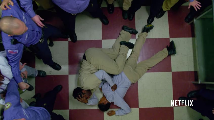 """Taystee laying on the floor with Poussey's body surrounded by guards and inmates on """"Orange is the New Black"""""""