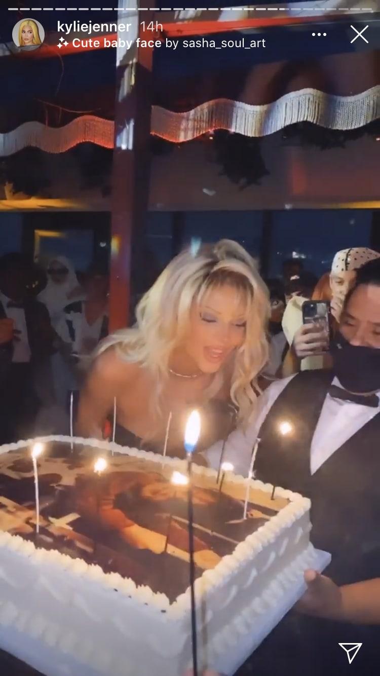 Kendall Jenner fantasiada de Pamela Anderson soprando velas de seu bolo de aniversário.