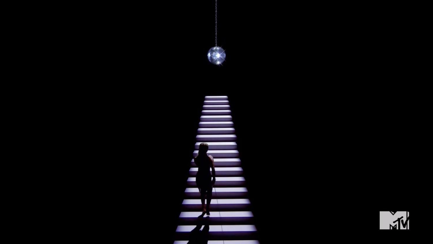 Miley de costas e uma bola de espelhos degraus acima