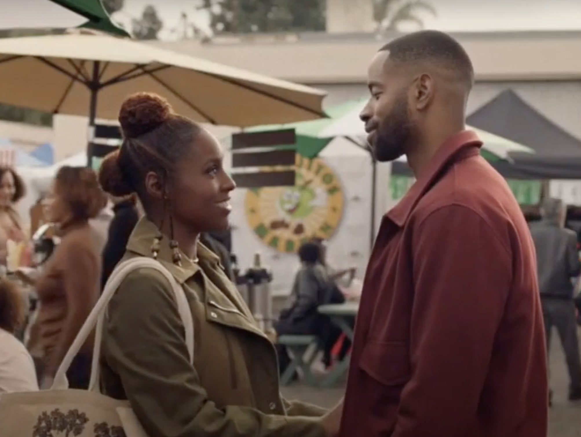 Issa and Lawrence hold hands at a farmers market