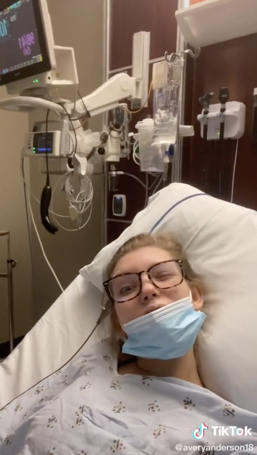 Avery in a hospital bed with a face mask on