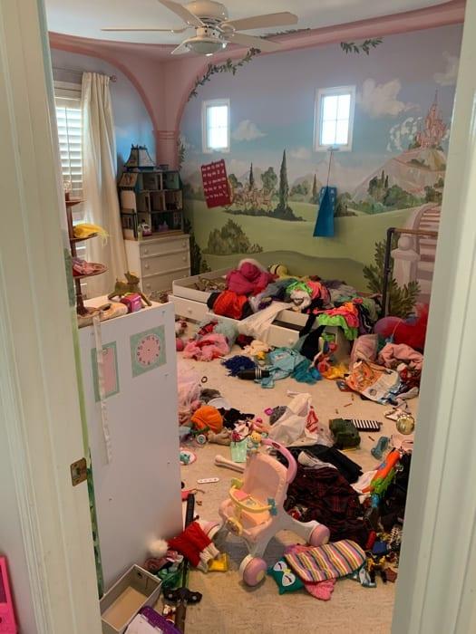 Um quarto de criança com todos os objetos no chão.