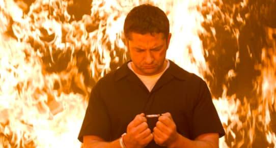 Imagem do ator Gerard Butler no filme. Ao fundo há várias chamas, como se fosse uma explosão ou um incêndio.