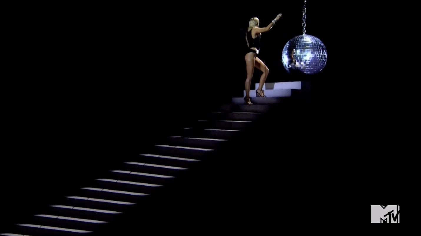 Miley subindo as escadas em direção à bola