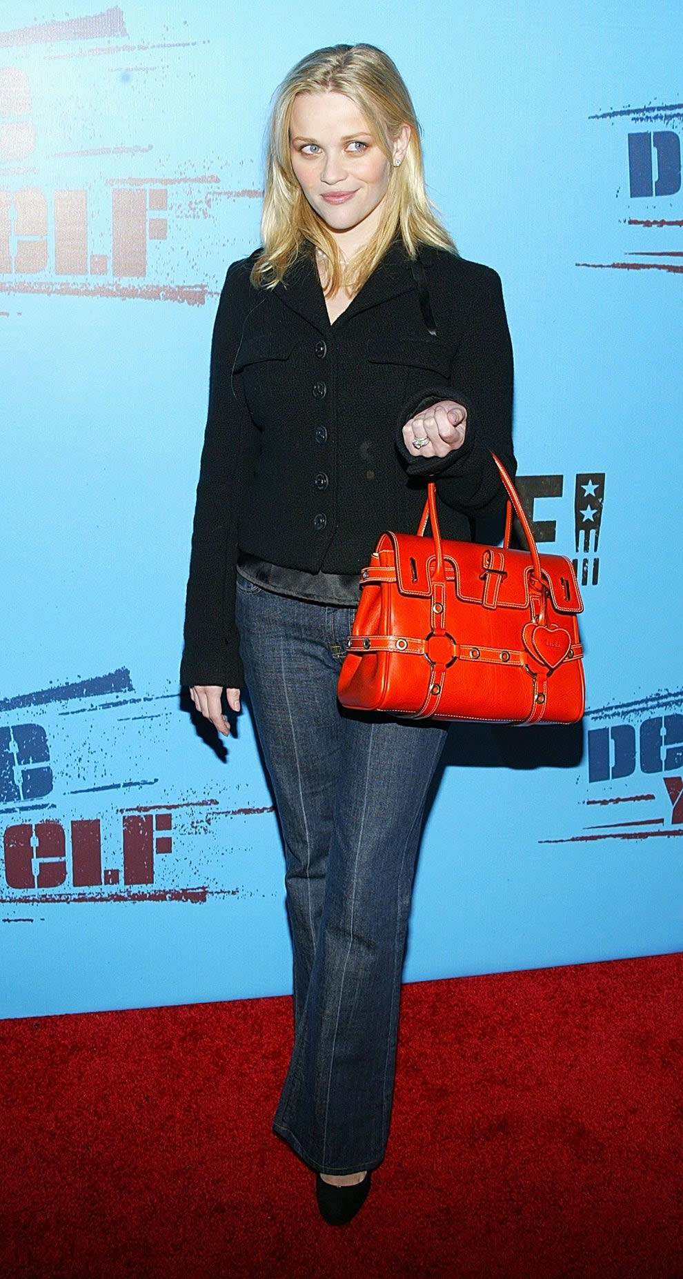 Reese wears a buttoned jacket, wide leg jeans, and holds a giant red purse.
