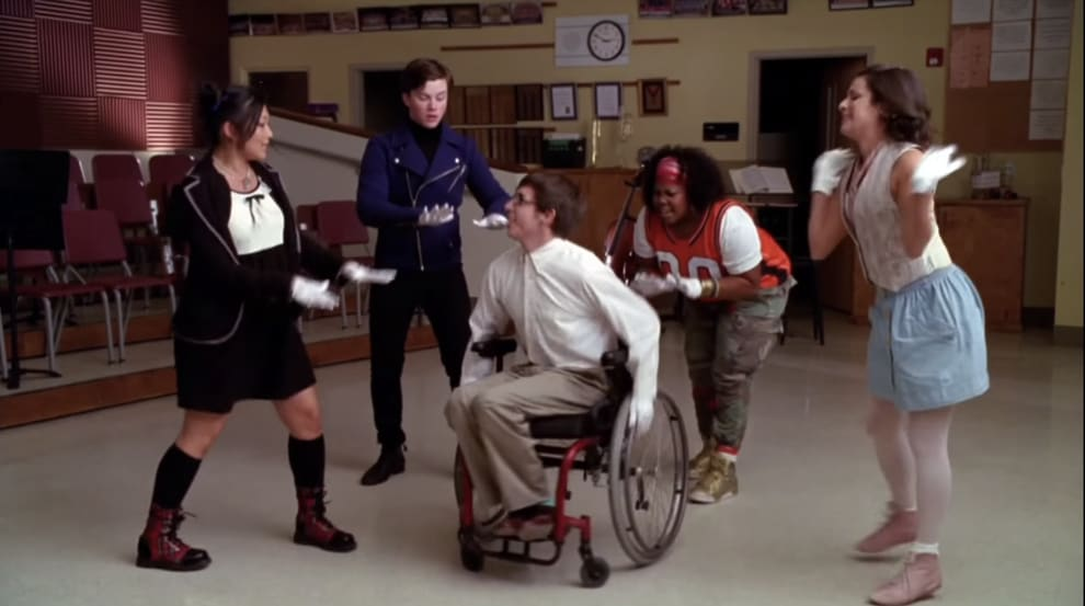 Artie, who uses a wheelchair, sings the lead vocals in a group number.