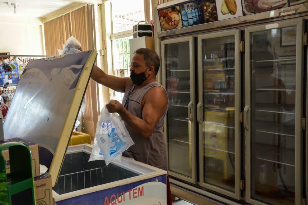 Homem segurando dois sacos de gelo derretido.