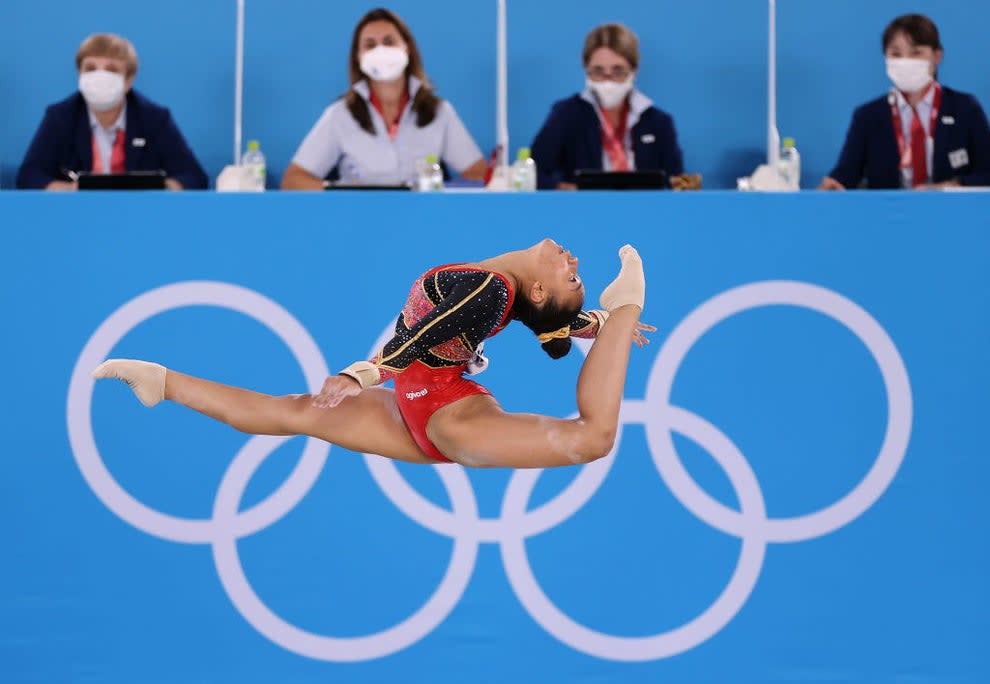 An airborne gymnast with one of their legs extended behind them and near their head