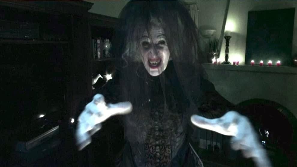 Imagem de uma personagem assustadora, que na verdade é um fantasma. Ela veste uma roupa toda preta e um véu preto cobre seu rosto.