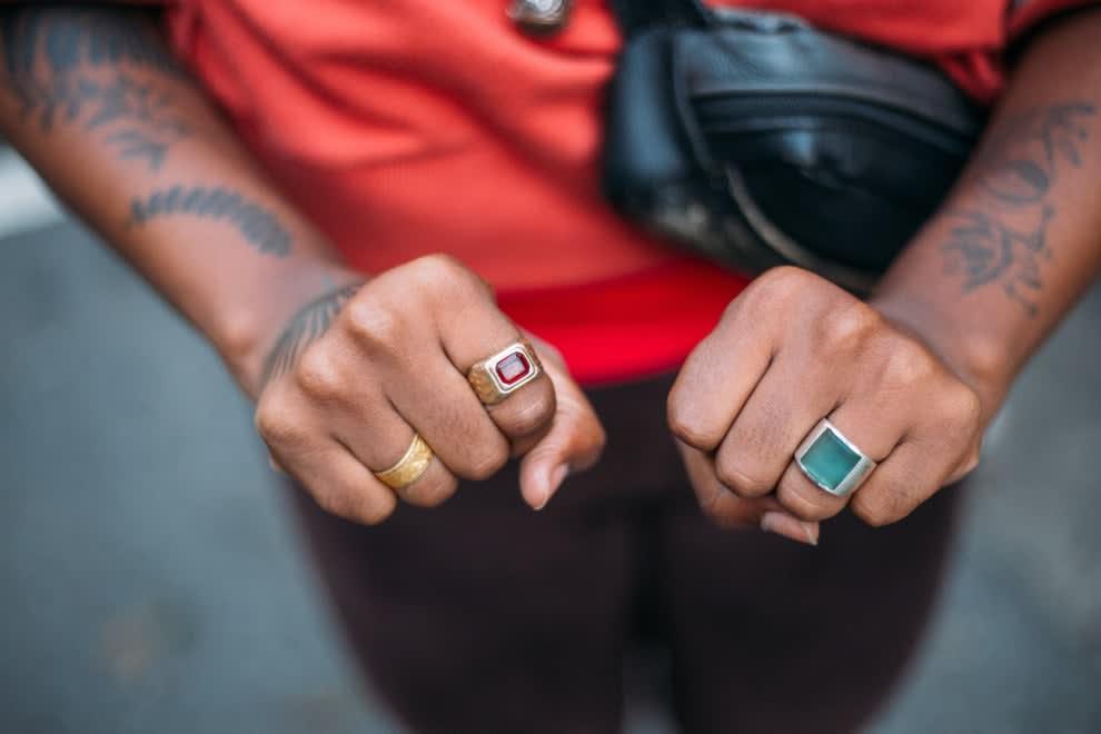 Duas mãos de jovem negro mostrando tatuagens diversas e anéis coloridos.