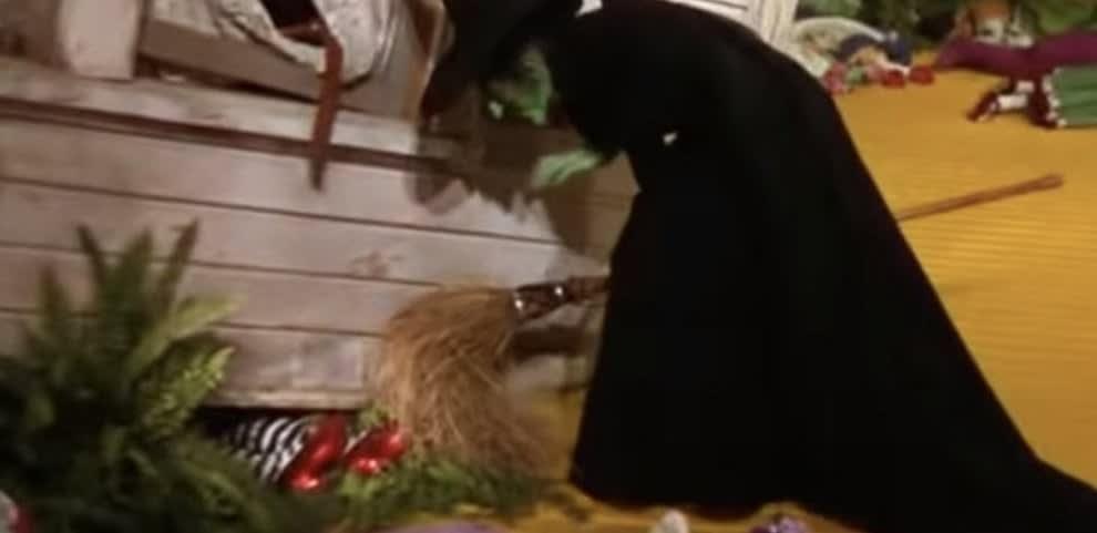 Bruxa olhando os sapatos vermelhos embaixo da casa