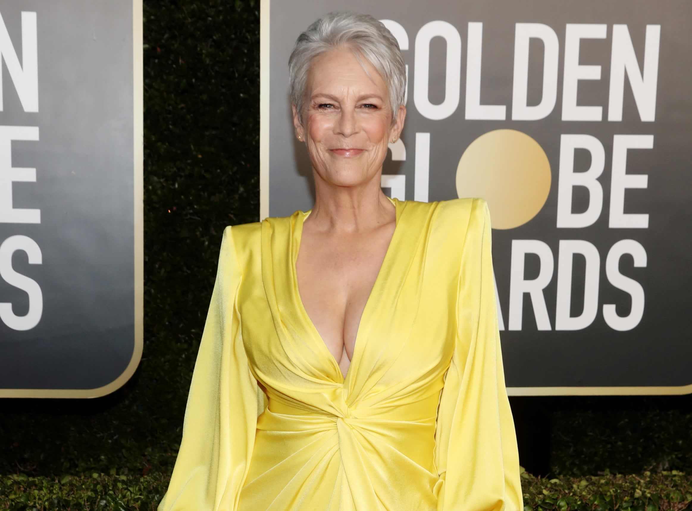 Jamie smiles while wearing a yellow dress with long sleeves and deep v neck