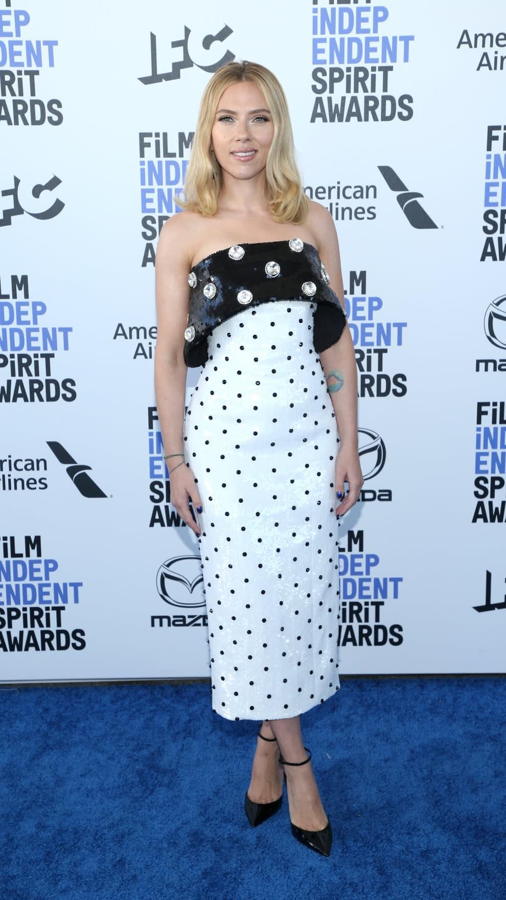Scarlett wears a tea-length dress with polka dots and giant polka dot gems on top.