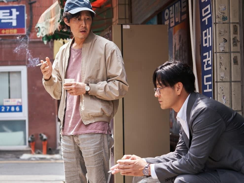 Gi-hun stands next to a seated Sang-woo; they both smoke