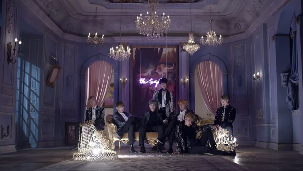 BTS sit in formalwear in a purple elaborately styled room with multiple chandeliers