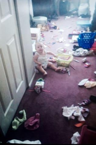 Foto antiga de um bebê em um cômodo com vários objetos jogados no chão.