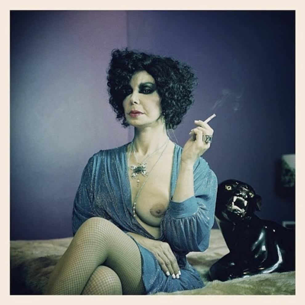 Claudia Wonder posando sobre uma cama, segurando um cigarro e exibindo um dos seios.