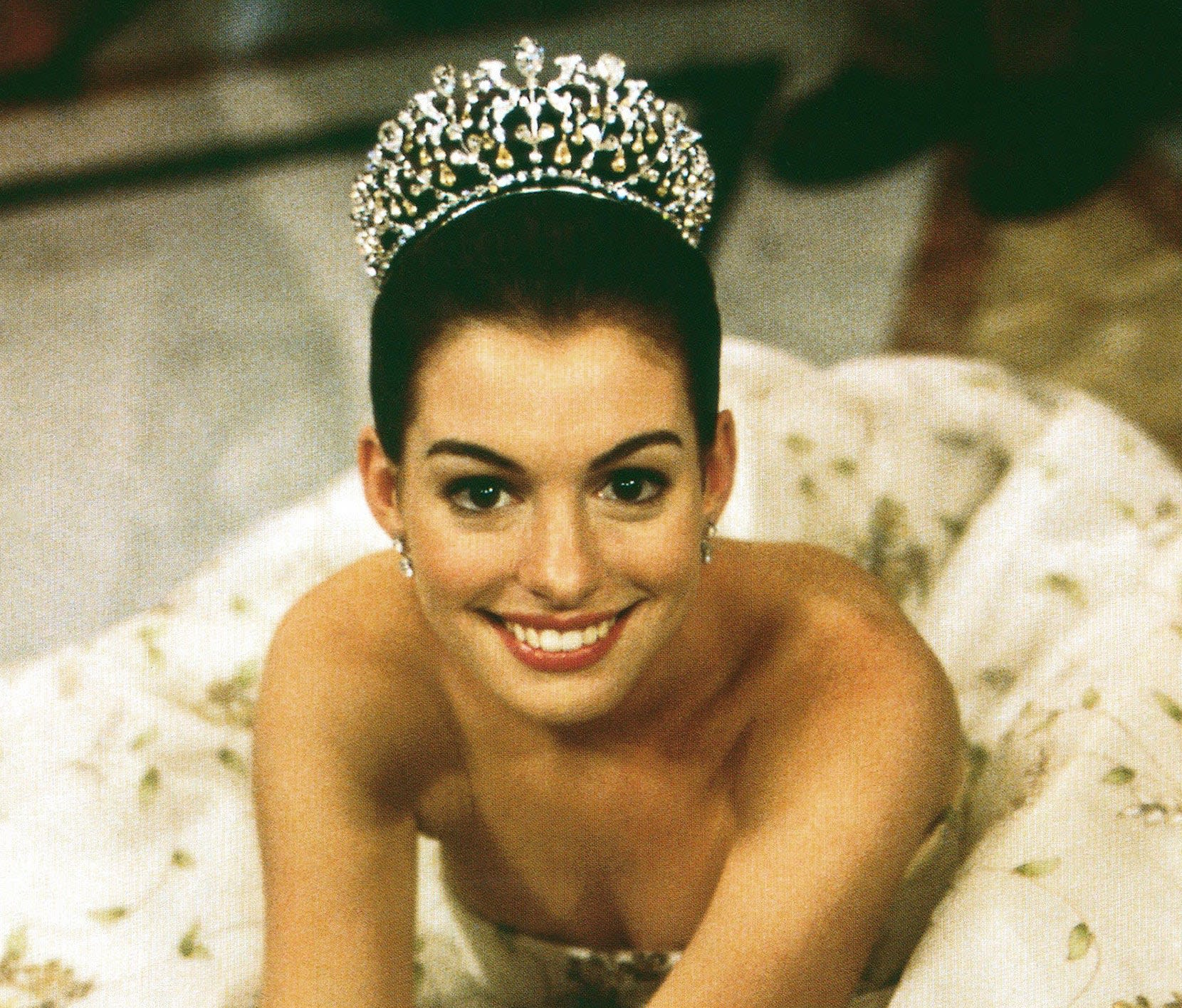 Mia sitting while wearing a strapless ball gown and an intricate tiara