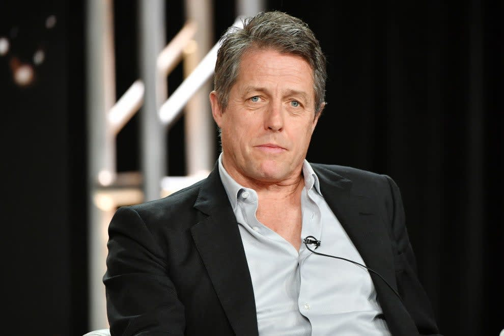 Hugh Grant with an open neck shirt and jacket, looking serious