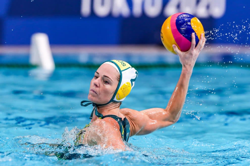 A water polo player wearing the cap and getting ready to throw the ball