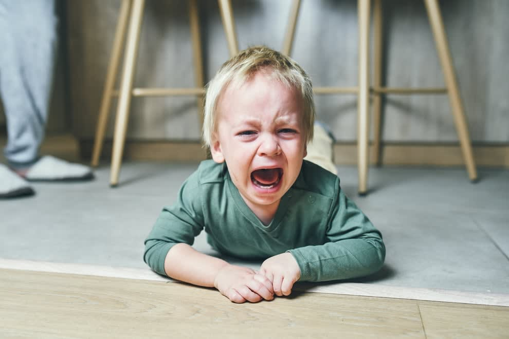 A young boy on the floor crying