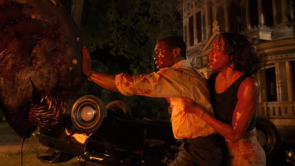 Cena da série Lovecraft Country onde vemos dois personagens ensanguentados fugindo de um monstro.