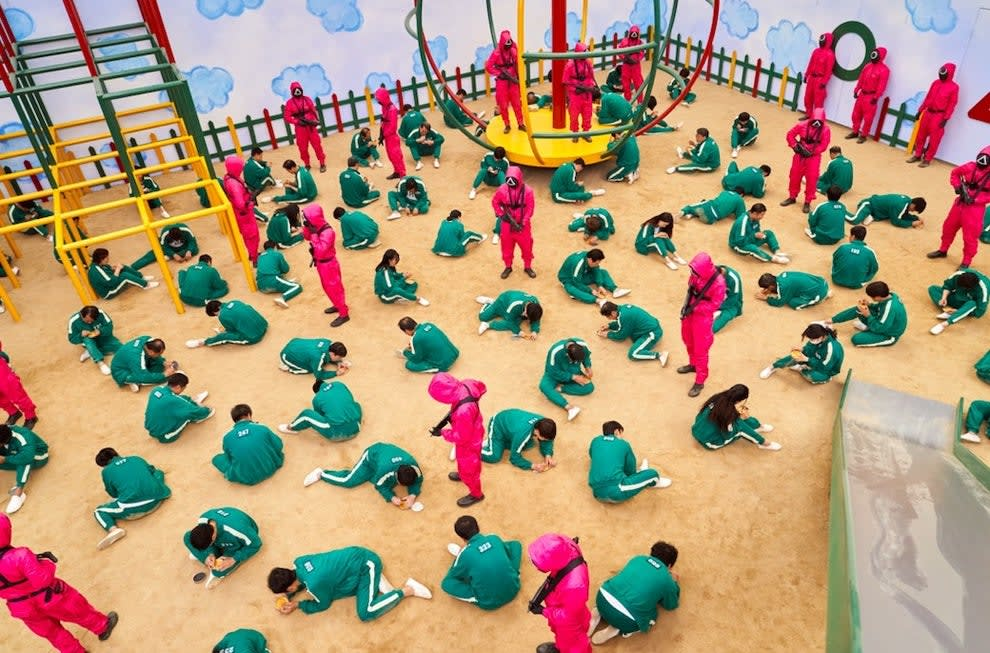 The contestants kneel on the ground in an oversized playground setting with guards watching over them