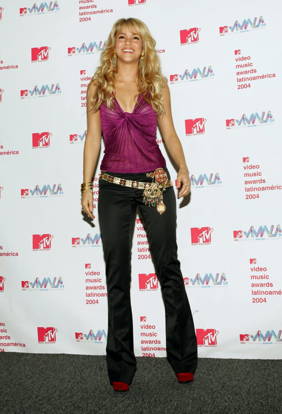 Shakira wears a halter top with jeans and a big jewelled and embellished belt hanging off of her right hip.