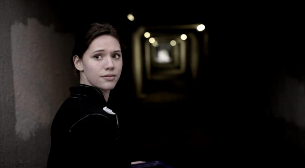 Imagem da atriz Katie Parker no filme Absentia. Ela está parada em um corredor mal iluminado.