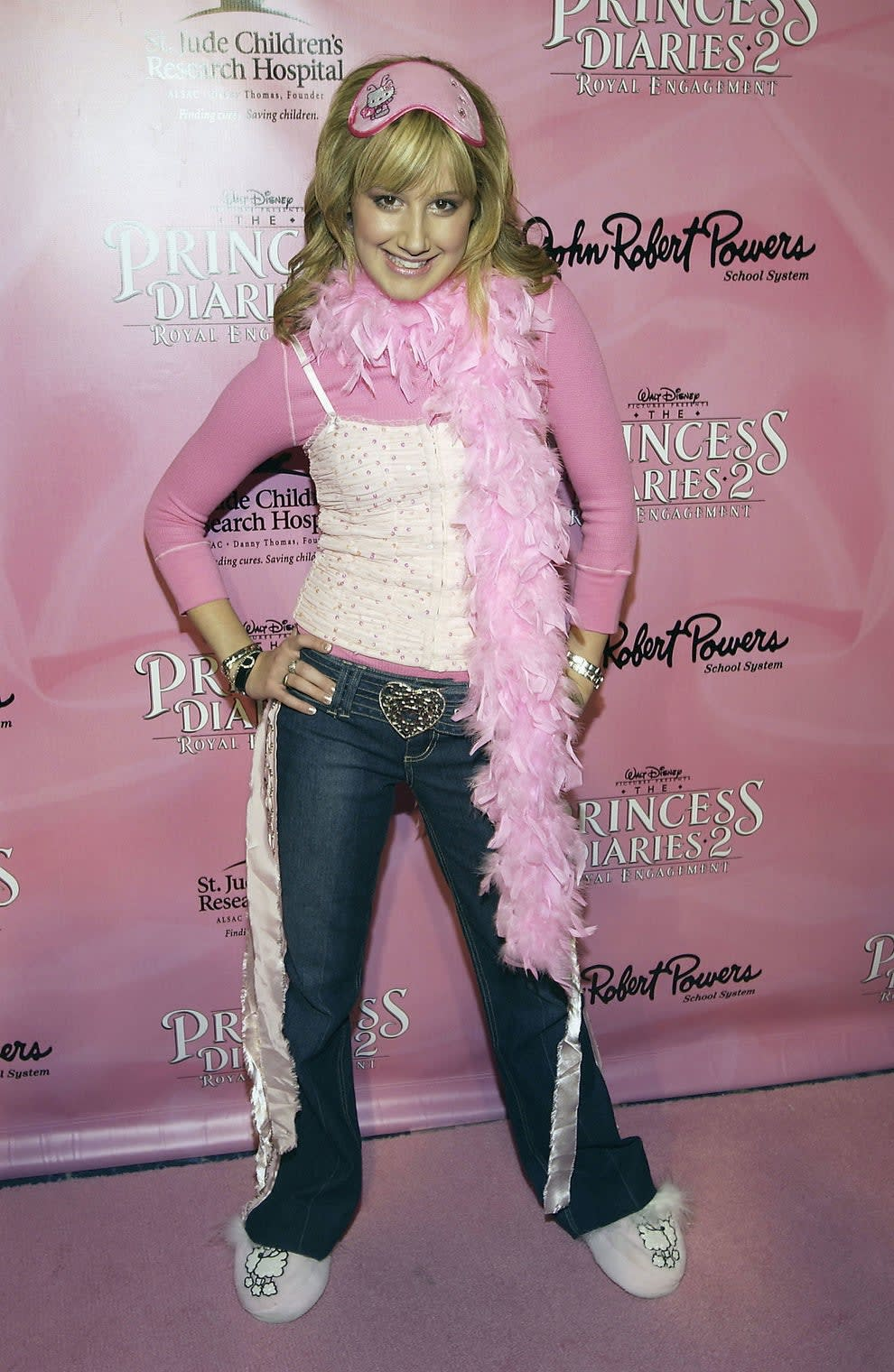 Ashley wears a printed tank top layered on top of a long sleeved shirt. She has a feather boa, slippers with poodles on them, and a sleep mask on her head.he also wears jeans with pink ribbons coming from the side and a belt in the shape of a heart.