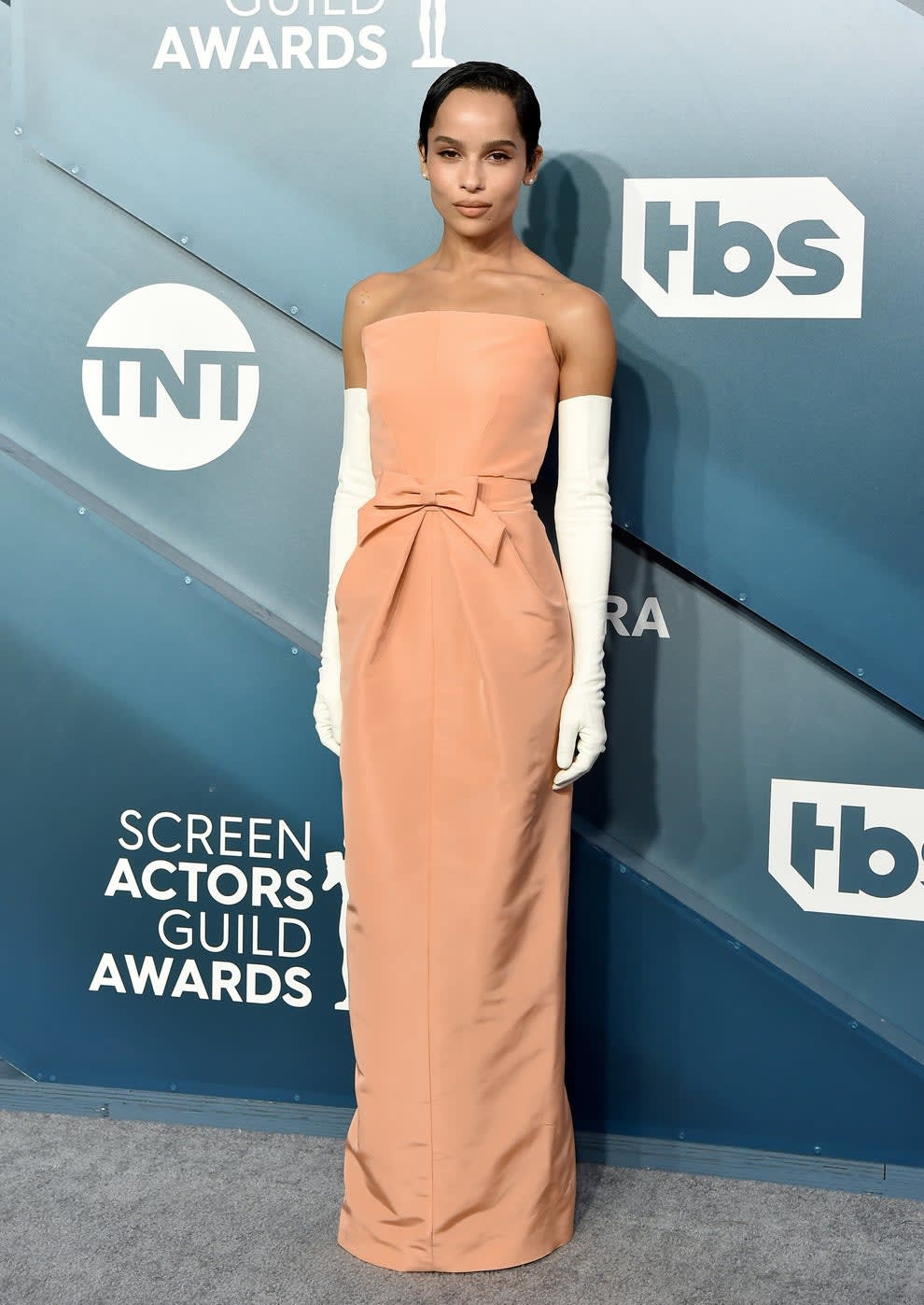 Zoe at a step and repeat in long sleeveless gown with arm length gloves