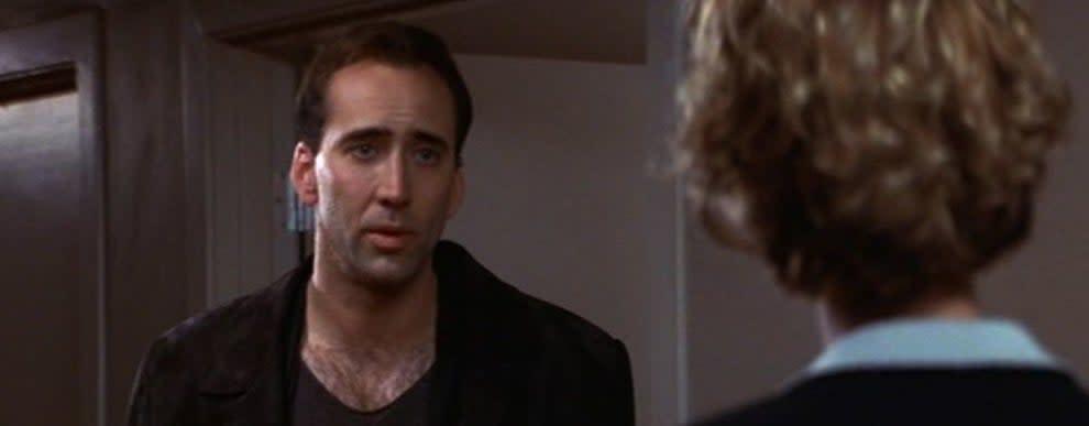 Imagem de Nicholas Cage no filme. Ele conversa com uma personagem que está de costas para a câmera.