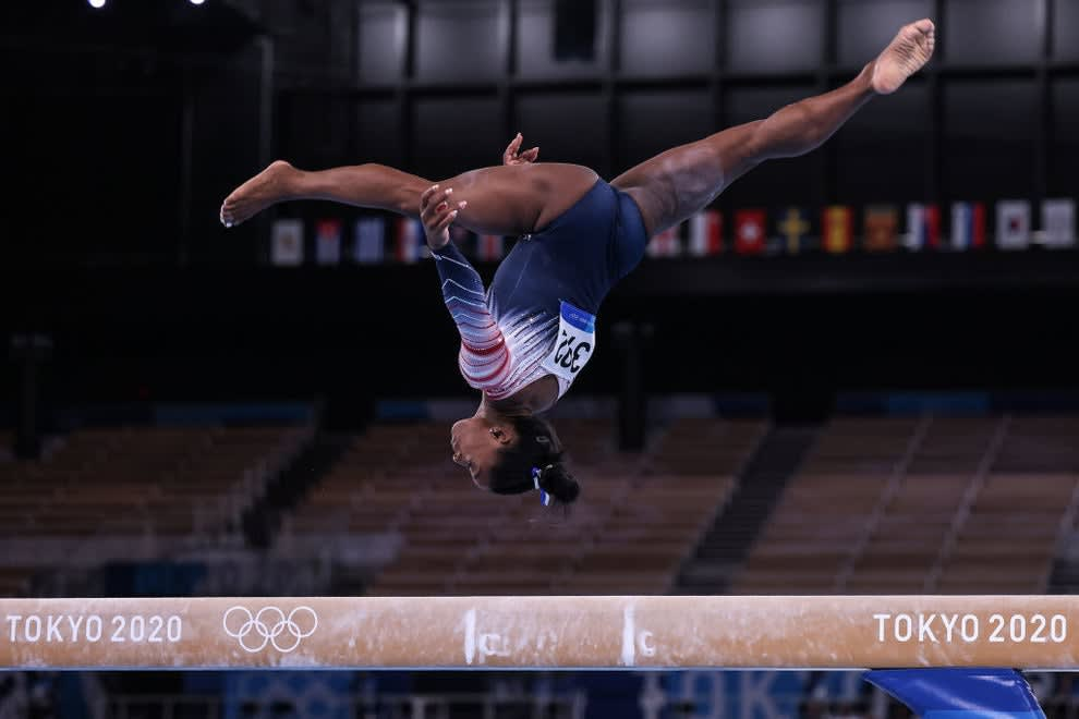 Simone upside down as she's mid-air over the balance beam