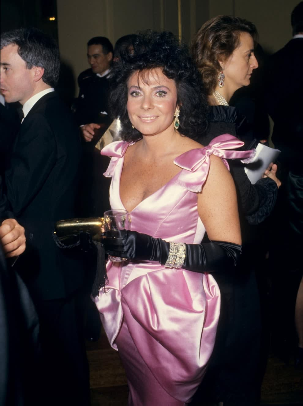 Patrizia at an event rocking teased hair and a satin gun with gloves