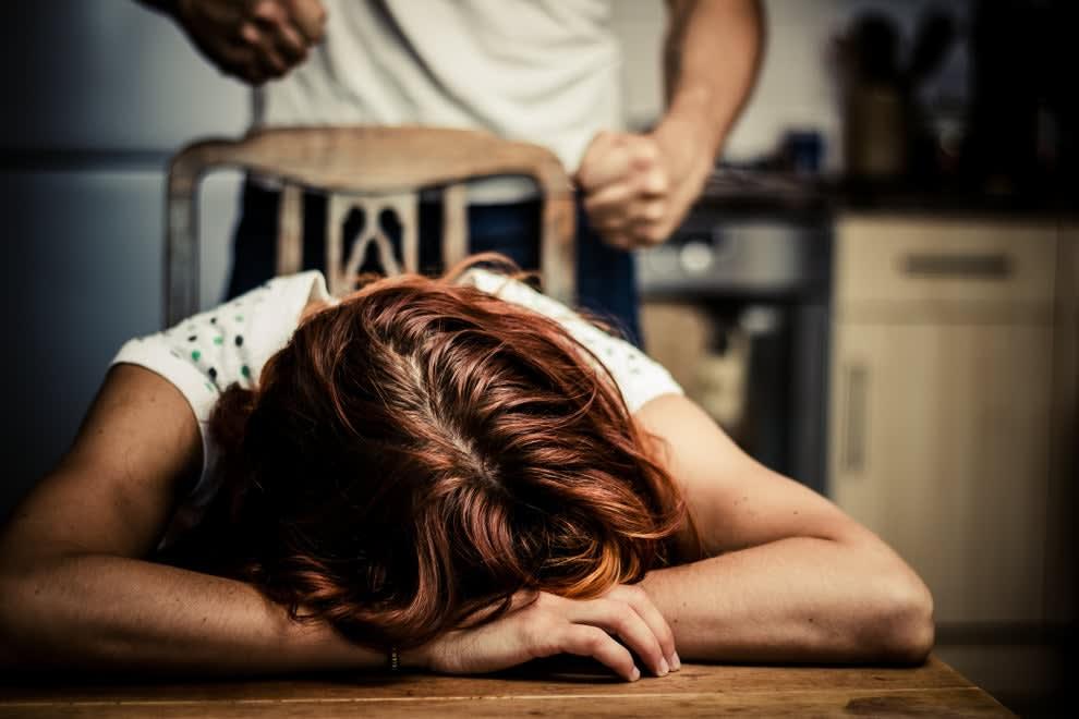 mulher com cabeça deitada na mesa e homem com punhos cerrados atrás dela