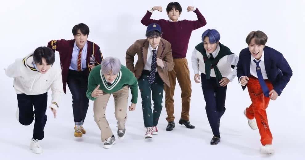 BTS run towards the camera in a white studio wearing preppy clothes