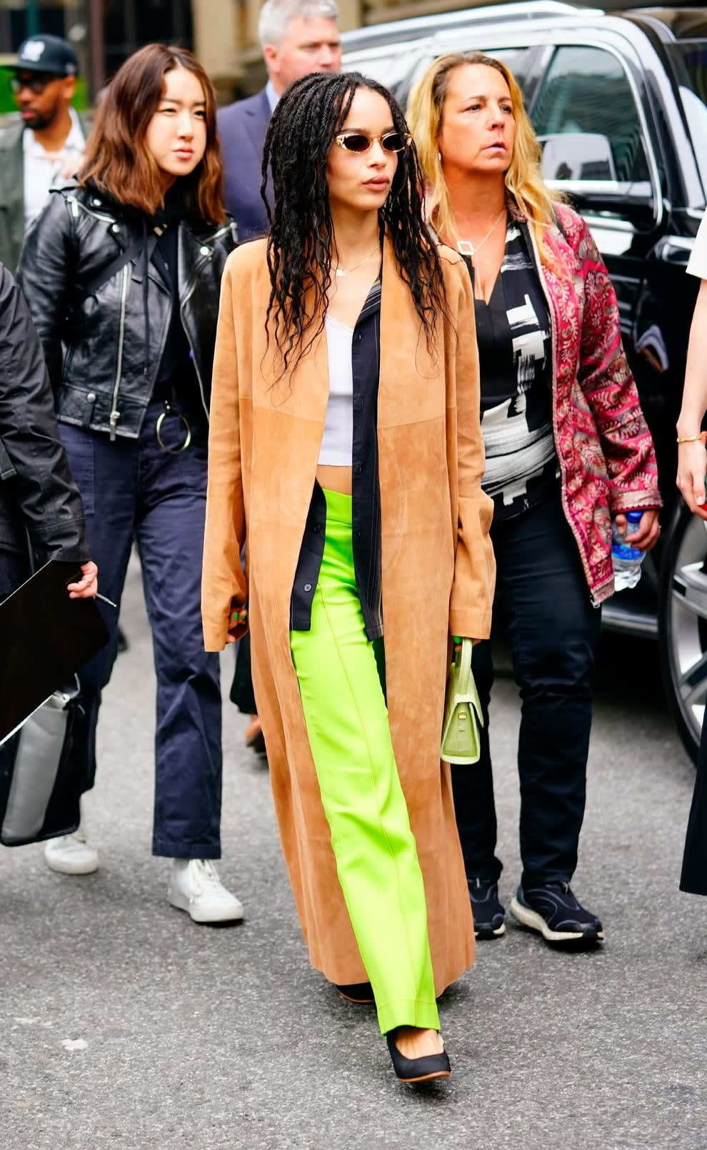 Zoe outside in bright pants, long suede coat, shades