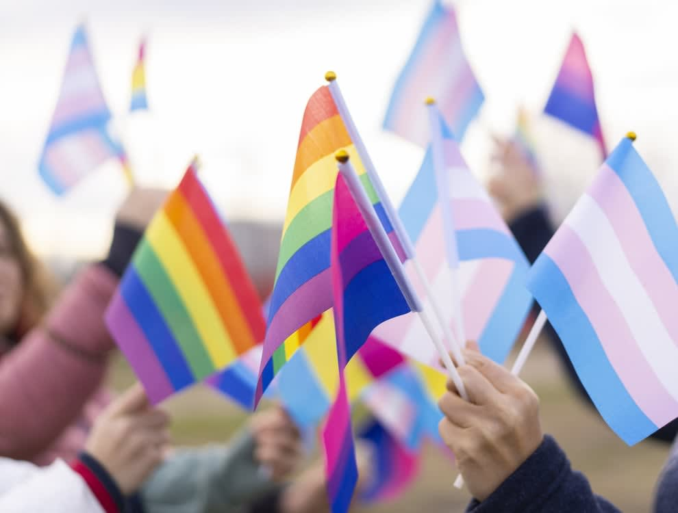 Woman holding Pride and Trans flags
