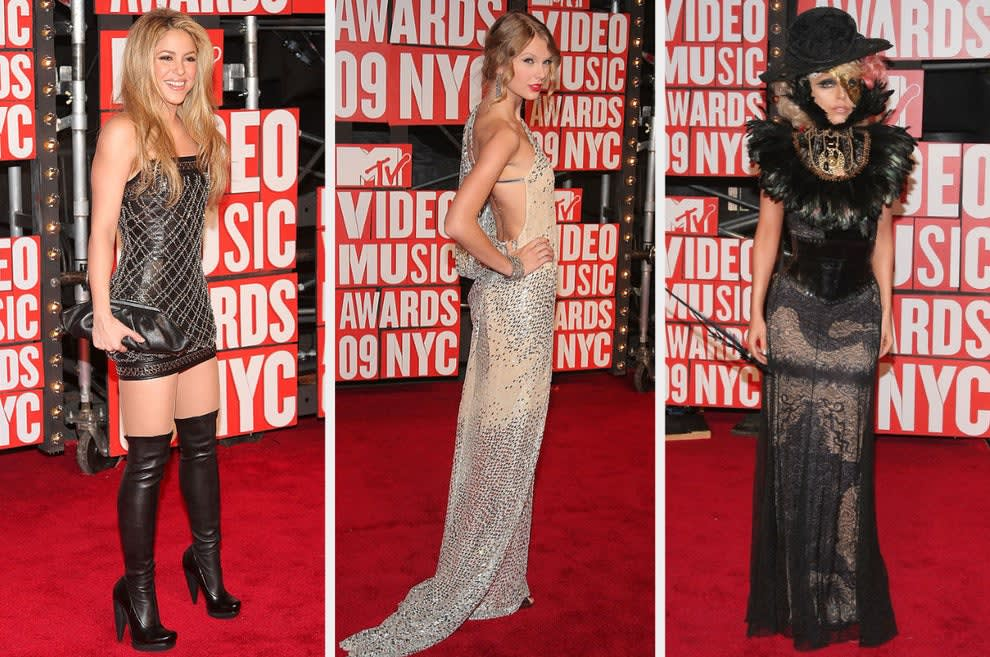Shakira wears a studded mini dress with thigh-high boots, Taylor wears a flowy backless gown with jewel details, Lady Gaga wears a lace gown with feathers and half a masquerade mask