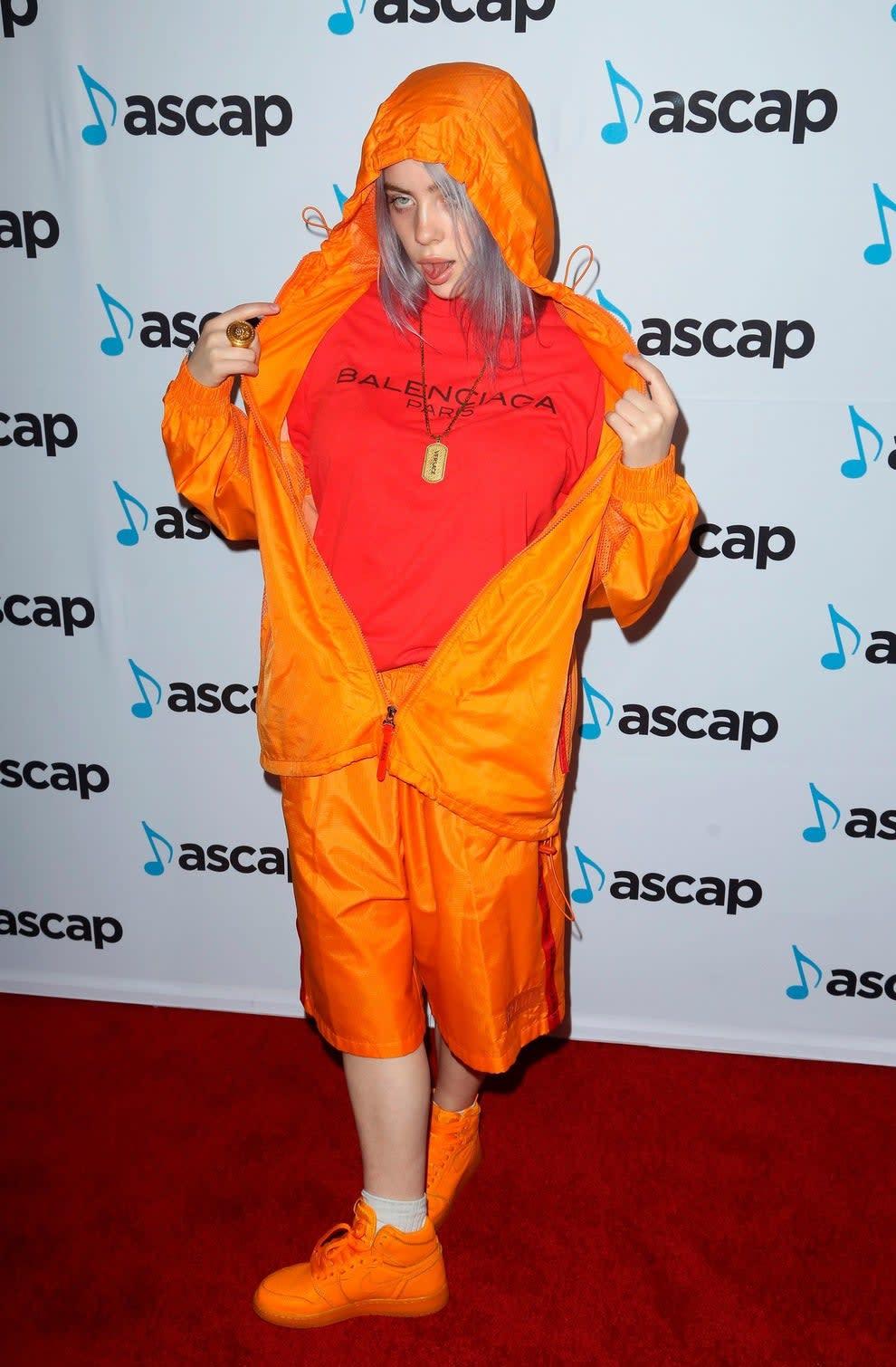 Billie no tapete com conjunto laranja Balenciaga