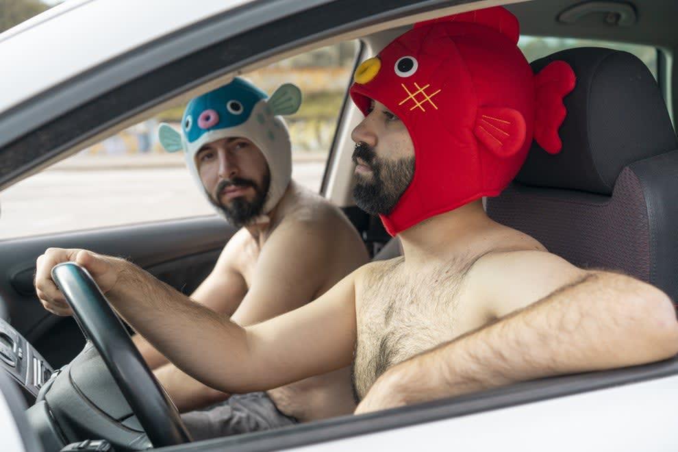 shirtless men wearing fish hats and driving a car