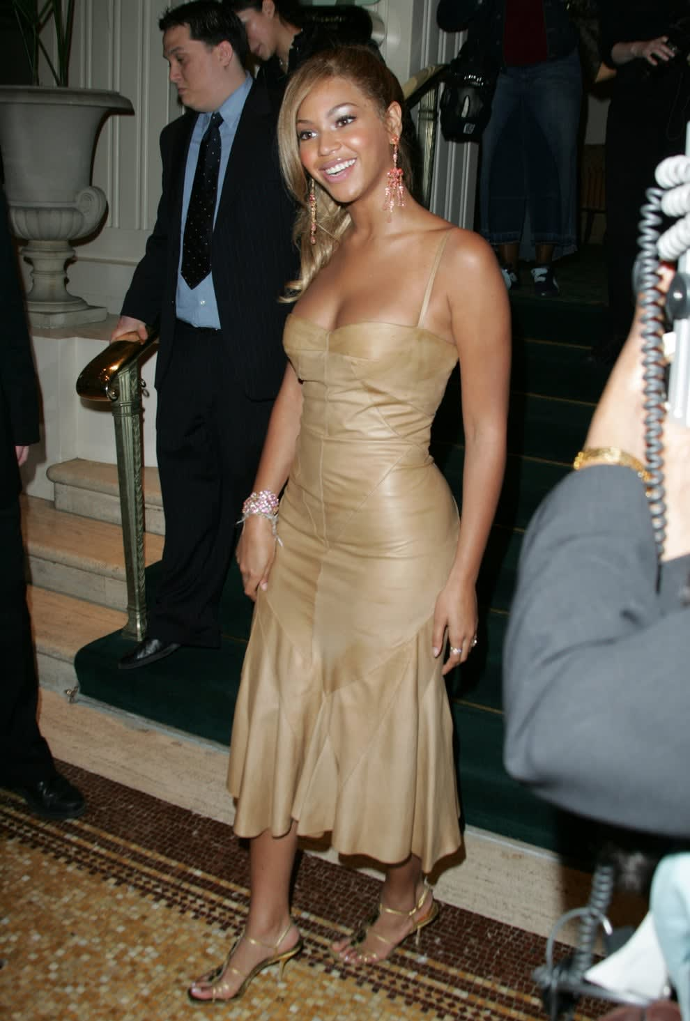Beyoncé wears a beige suede dress with sandals and her hair in a side, low ponytail
