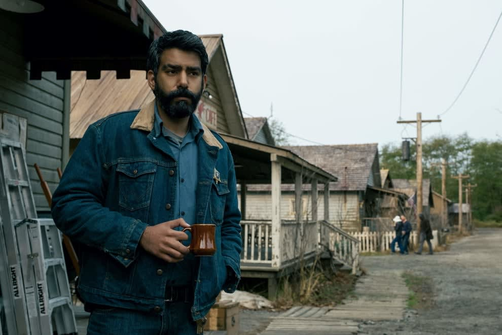 A man standing outside a home holding a mug