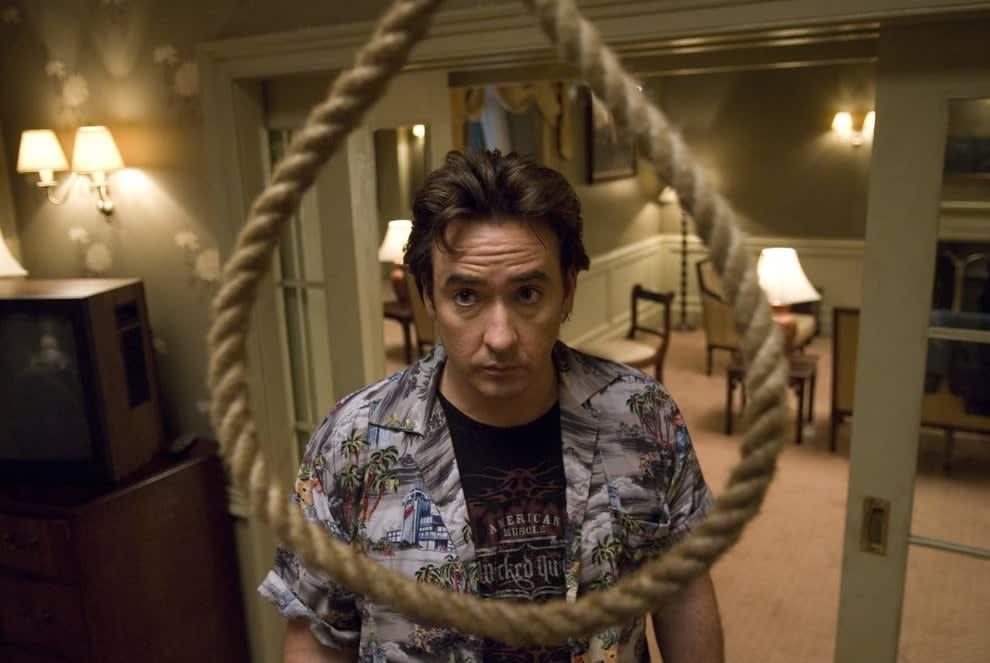 Imagem mostra o ator John Cusack em uma cena do filme 1408. Ele está encarando uma forca.